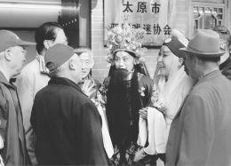 吴忠、阎惠珍等艺术家去银马河公园向金曲爱好者学习技巧。