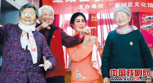 平剧演员手拉手教福利院的老人在舞台上行走和一些基本的鞠萍手势。